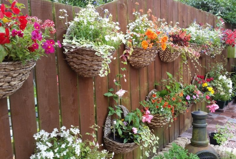 Корзины с цветами на заборе