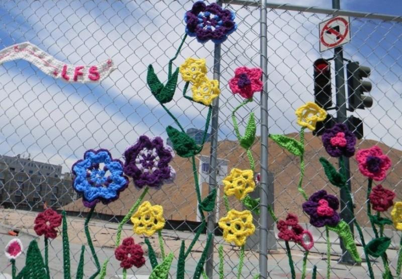 Вязанные цветы на заборе
